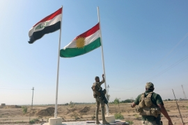 A member of the Iraqi forces takes down the Kurdish flag in Kirkuk [Reuters]