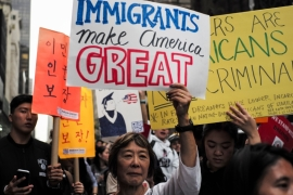 Protesters hold up signs during a pro-immigrant demonstration near the Trump Tower in New York [File: Jewel Samad/AFP/Getty Images]