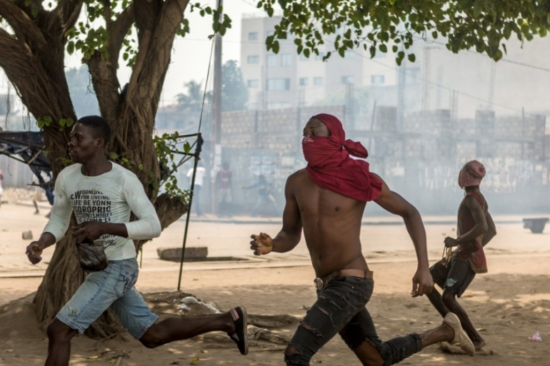 Protesters run during clashes with security forces during an anti-government protest in Lome, Togo, on October 18 [Yanick Folly/AFP/Getty Images]