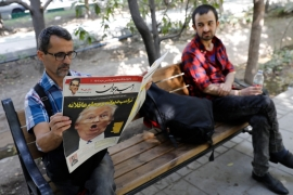 An Iranian man reads a copy of the daily newspaper 'Omid Javan' with a headline that reads in Persian 'Crazy Trump and logical JCPOA' [AFP/Getty Images]