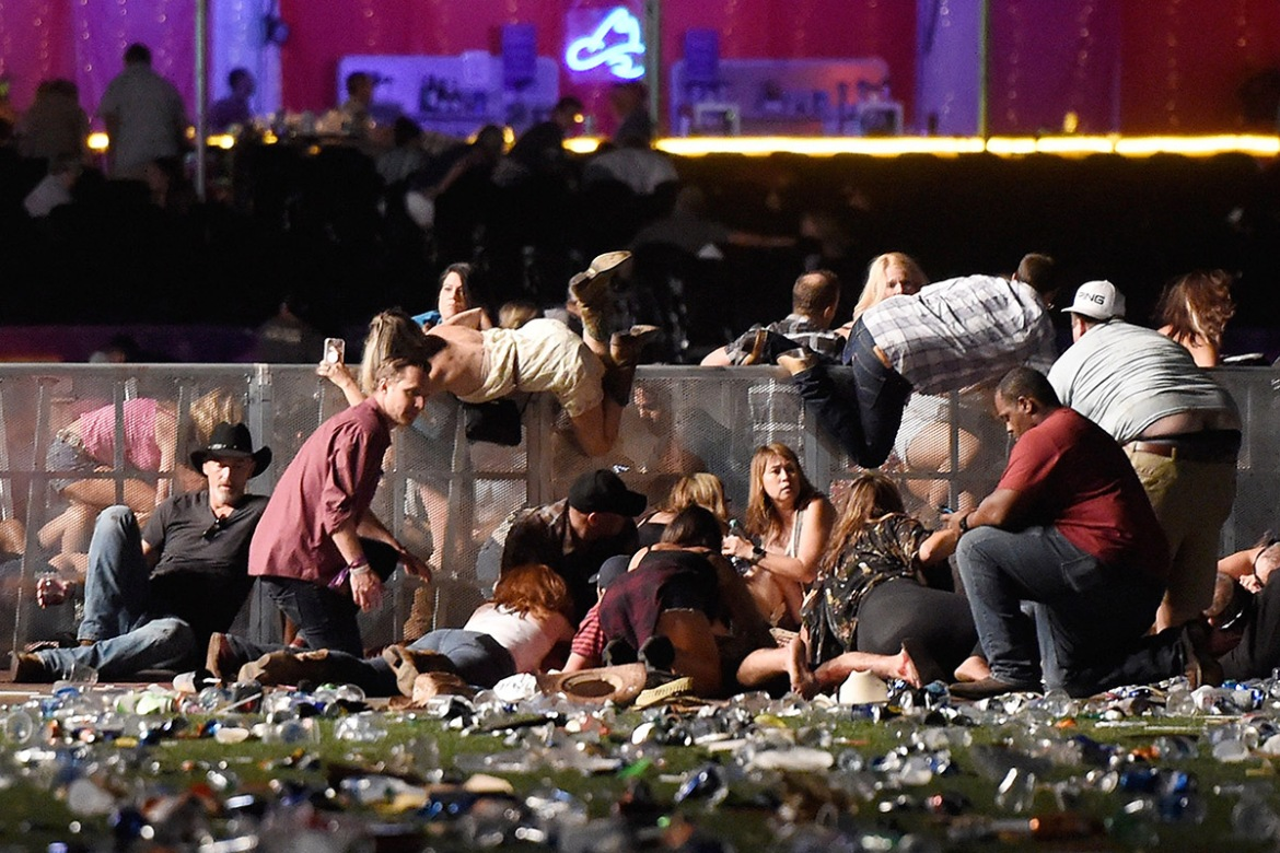People scramble for shelter at the Route 91 Harvest country music festival after gunfire. [David Becker/Getty Images]