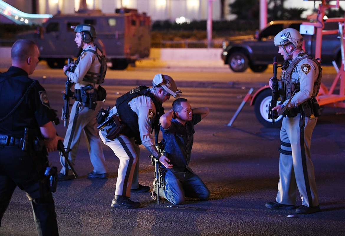 Police officers stop a man who drove down Tropicana Avenue, near Las Vegas Boulevard, which had been closed after a mass shooting at a country music festival. [Ethan Miller/Getty Images]