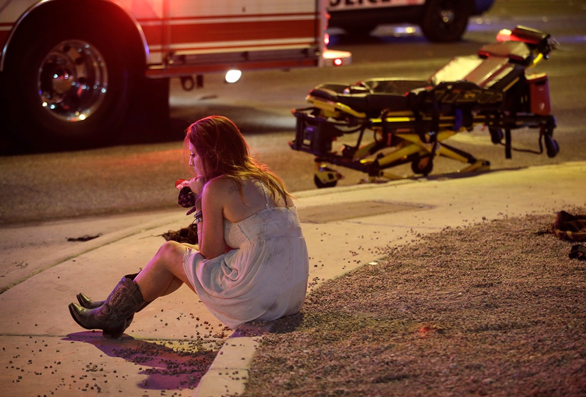 A woman sits on a kerb at the scene of a shooting outside of a music festival along the Las Vegas Strip. Multiple victims were being transported to hospitals after a shooting late Sunday at the festival. [John Locher/AP Photo]