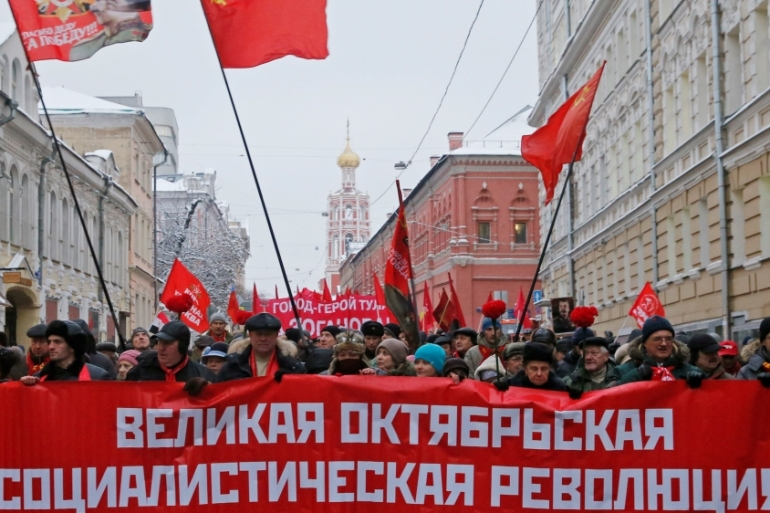 Russian citizens carry a banner reading 'Great October Socialist Revolution' during a rally marking the anniversary of the 1917 Bolshevik revolution in central Moscow, Russia [Maxim Zmeyev/Reuters]