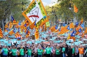 People wave Catalan flags and placards during a demonstration following the imprisonment of their two leaders Jordi Sanchez and Jordi Cuixart, in Barcelona, Spain [Ivan Alvarado/Reuters]