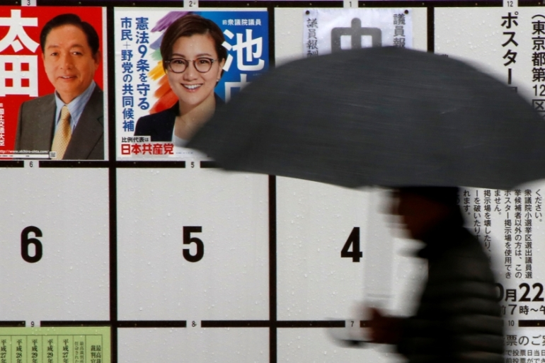 A man walks in the rain past election posters near a polling station in Tokyo, Japan [Issei Kato/Reuters]