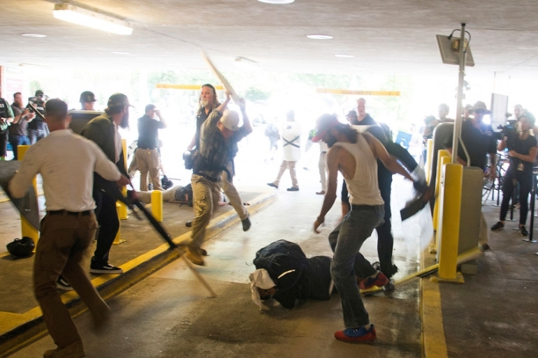 In this Saturday, August 12, 2017, photo, DeAndre Harris is assaulted in a parking garage beside the Charlottesville police station after a white nationalist rally in Charlottesville, Virginia [File: Zach Roberts/AP Photo]