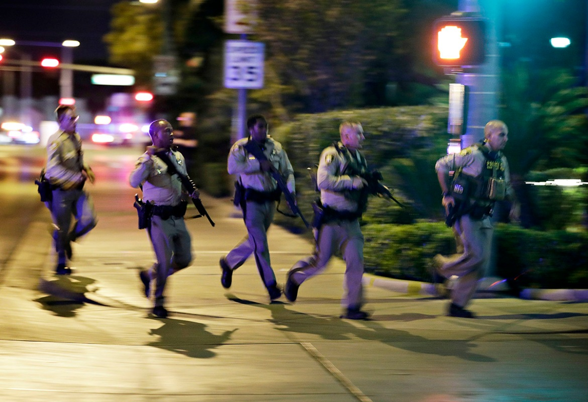 Police run to cover at the scene of a shooting near the Mandalay Bay resort and casino on the Las Vegas Strip. [John Locher/AP Photo]