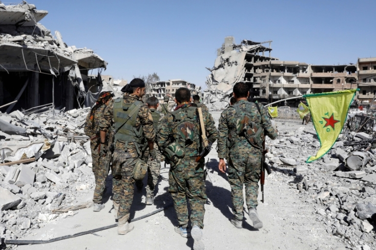 Fighters of Syrian Democratic Forces walk past the ruins of destroyed buildings near the National Hospital after Raqqa was liberated from the Islamic State fighters [Reuters/Erik De Castro]