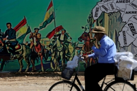 A man rides a bike near a mural supporting the referendum for independence of the Kurdish region in Erbil, Iraq [Alaa Al-Marjani/Reuters]