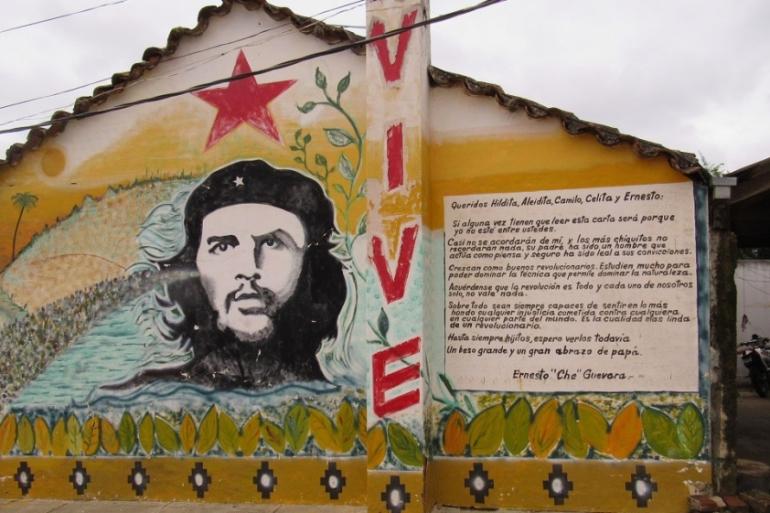 A portrait of Che and a letter to his children is painting on a building Vallegrande [Lew Friedman/Al Jazeera]