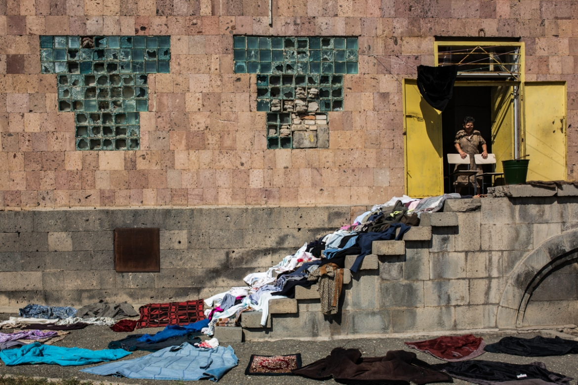 Karine lays out her clothes to dry in the sun at the entrance of the abandoned building where she has been living for 28 years. [Yulia Grigoryants/Al Jazeera]