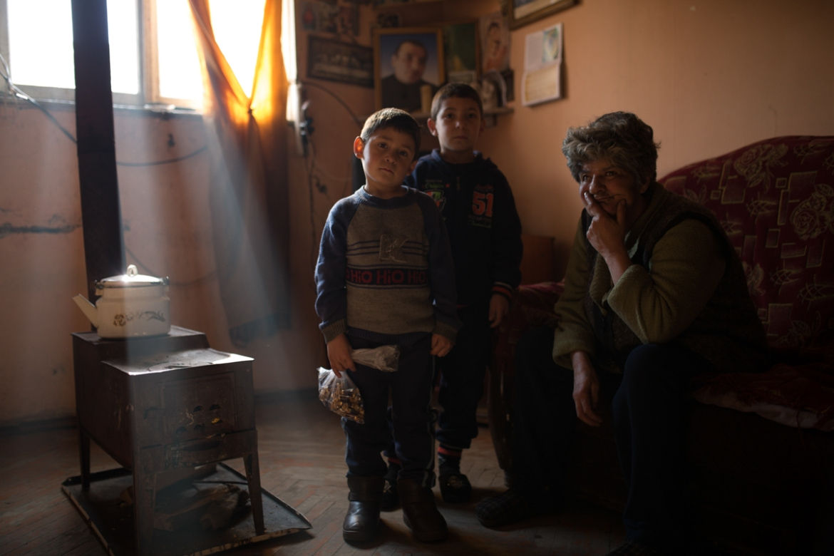 Syuzanna's brothers - Suren, aged 5, and Levon, aged 7, greet a visiting relative in their single room apartment, just few days after their father committed suicide. In Armenia, during the first 40-day mourning period, relatives and neighbours visit the family to pay their respects and offer support to the grieving family. [Yulia Grigoryants/Al Jazeera]