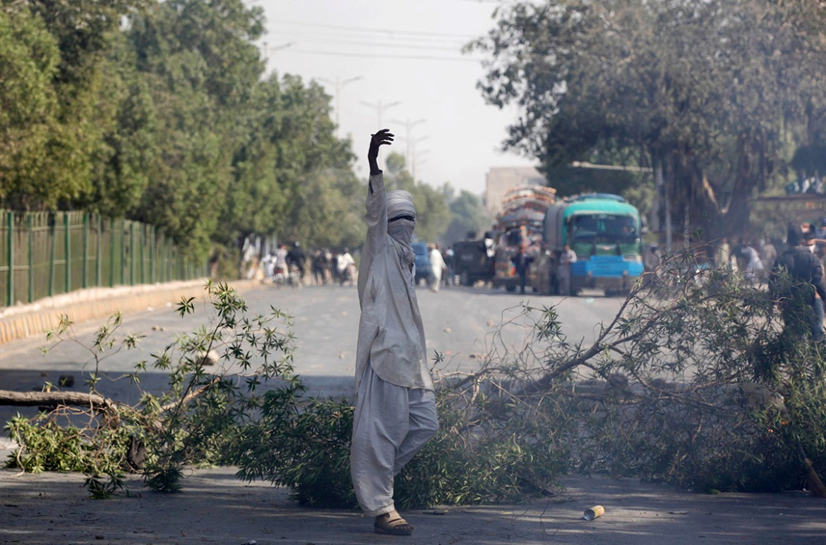 A supporter of the Tehreek-e-Labaik Pakistan  gestures after blocking the main road leading to the airport in Karachi. [Akhtar Soomro/Reuters]
