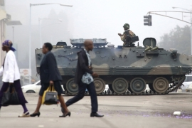 People walk by an armed soldier patrolling the streets of Harare [The Associated Press]