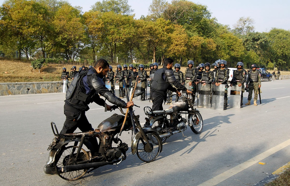 Police retrieve their motorcycles which were burned during clashes with protesters near the Faizabad junction in Islamabad. [Caren Firouz/Reuters]