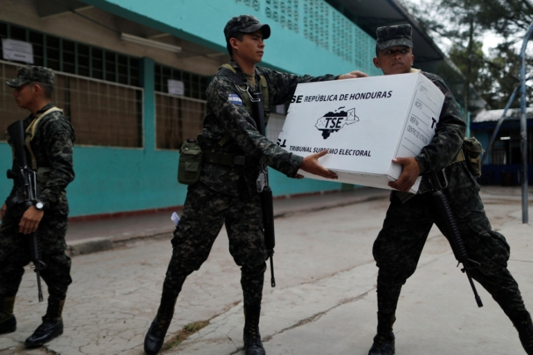 Soldiers unload election materials for distribution at voting stations ahead of the presidential election in Tegucigalpa, Honduras [Edgard Garrido/Reuters]