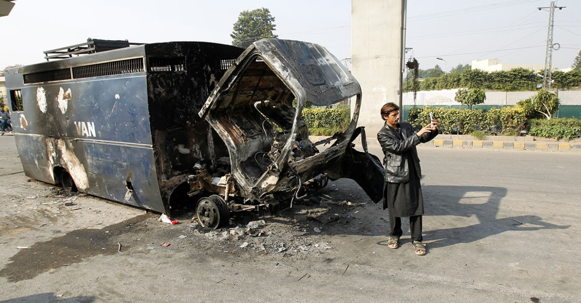 A passerby takes a selfie in front of a police prison van destroyed during clashes with police near the Faizabad junction in Islamabad. [Caren Firouz/Reuters]