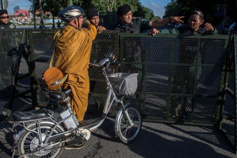 A foreign Buddhist monk is stopped by police forces at a barricade set up on one of the main avenues with access to the Supreme Court [Omar Havana/Al Jazeera]