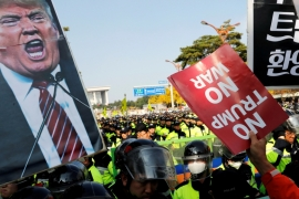 Anti-Trump protesters hold up signs in front of police officers near the South Korean National Assembly where US President Donald Trump made a speech, in Seoul on November 8 [Reuters/Kim Kyung-Hoon]