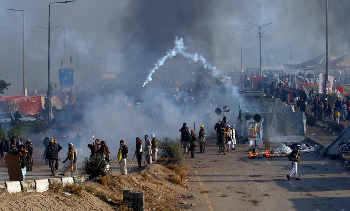 Protesters hurls back a tear gas shell fired by police during a clash in Islamabad. [Anjum Naveed/AP Photo]