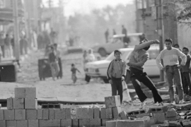 A youth throws stones in the direction of Israeli soldiers at the entrance to Bureij refugee camp in the occupied Gaza strip during the first intifada in 1987 [AP]