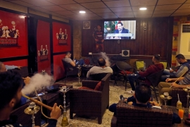 People in a Beirut cafe watch Hariri's interview on TV [Jamal Saidi/Reuters]