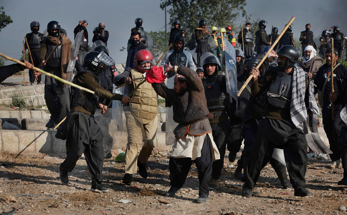 Pakistani police officers beat a protester during a clash in Islamabad. [Anjum Naveed/AP Photo]