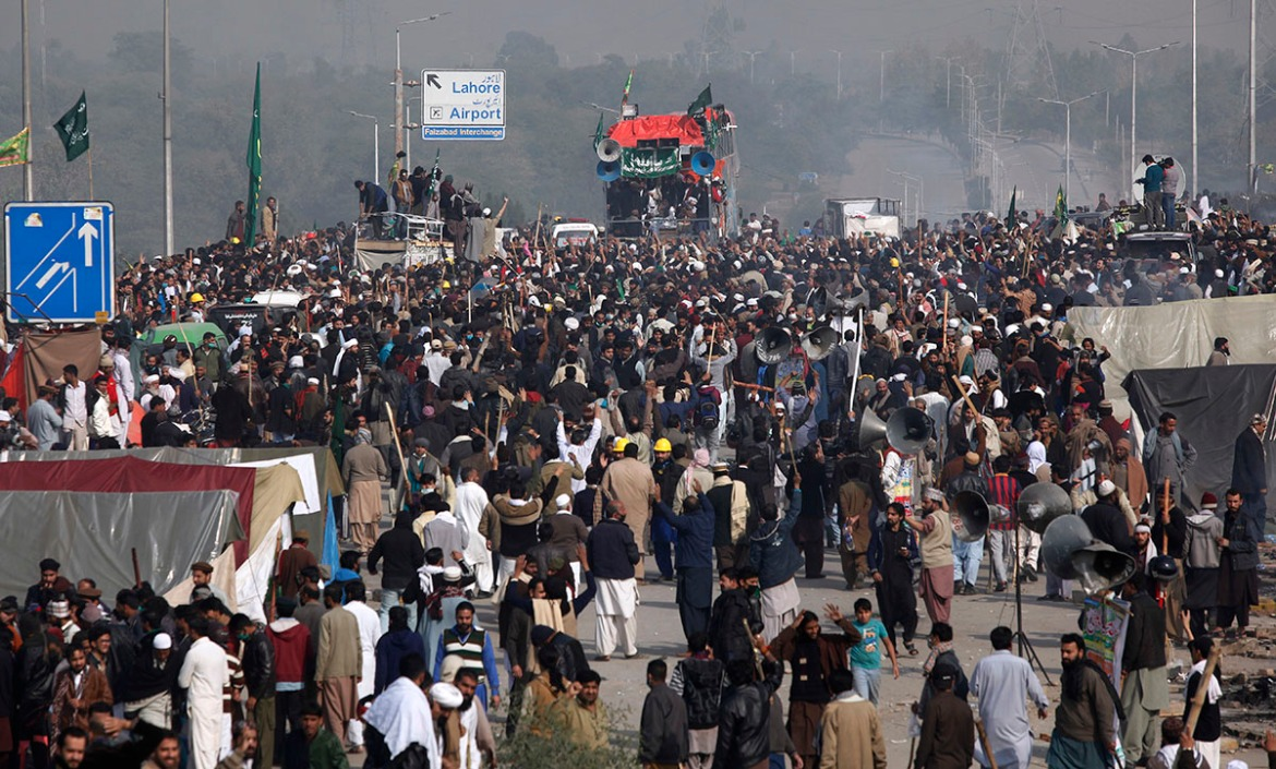 Protesters express their supports to their leadership after clash with police, in Islamabad. [Anjum Naveed/AP Photo]