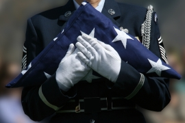 A soldier carries a folded American flag at a military funeral.  [Getty Images]