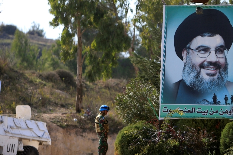 A peacekeeper of the UN Interim Force in Lebanon stands near a poster depicting Lebanon's Hezbollah leader Sayyed Hassan Nasrallah in southern Lebanon [Reuters/Ali Hashisho]