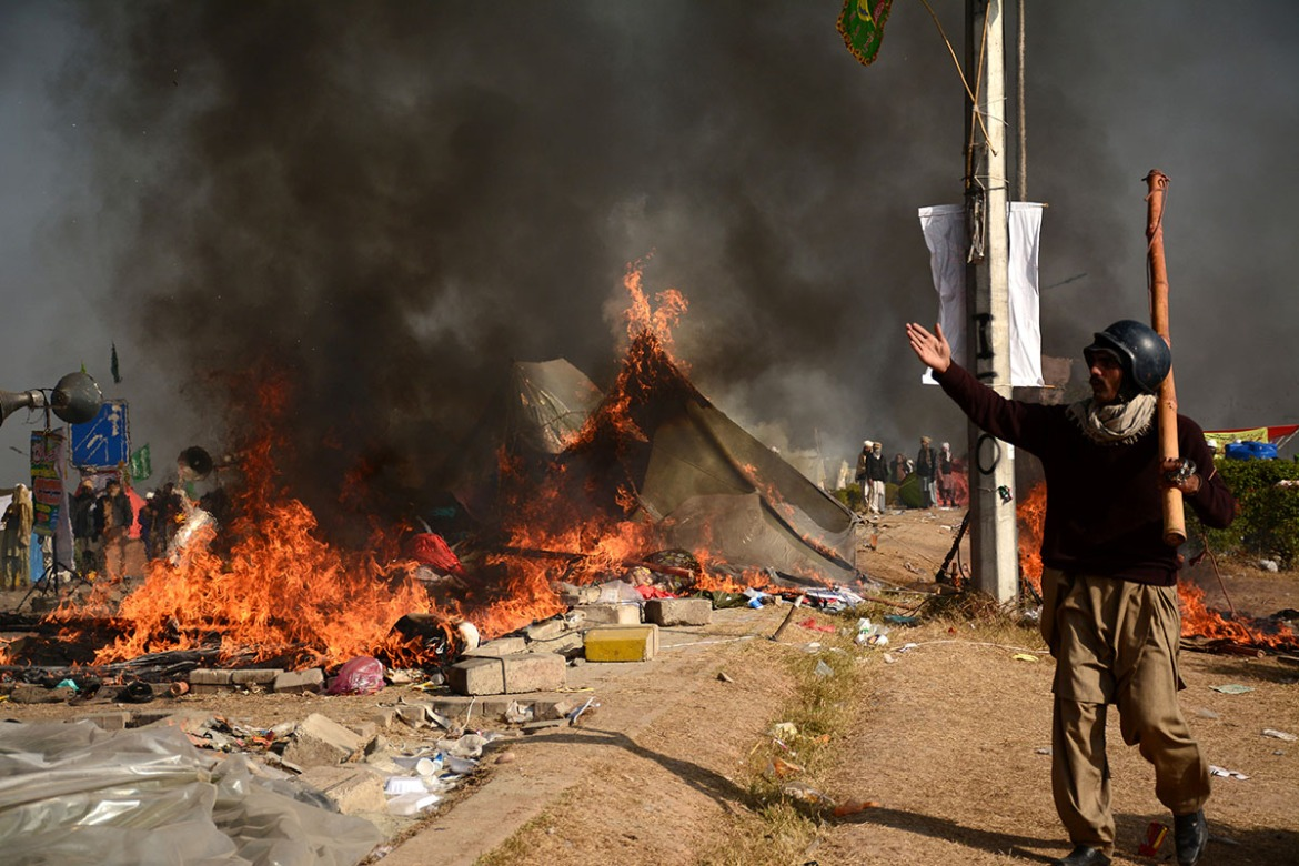 A protester walks near burning tents during clashes with police at Faizabad junction in Islamabad. [Reuters]