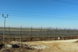 North Korea seen in the distance through a barbed-wire fence off South Korea's Gyodong Island on November 18 [Steven Borowiec/Al Jazeera]