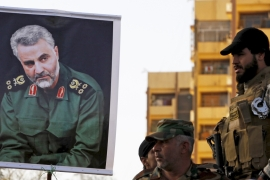 General Qassem Suleimani, pictured here in a portrait held by supporters, threatened Trump during a speech [File: Thaier al-Sudani/Reuters]