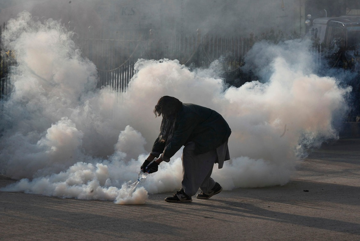 A protester pours water on a tear gas shell fired by police during a clash in Islamabad. [Anjum Naveed/AP Photo]