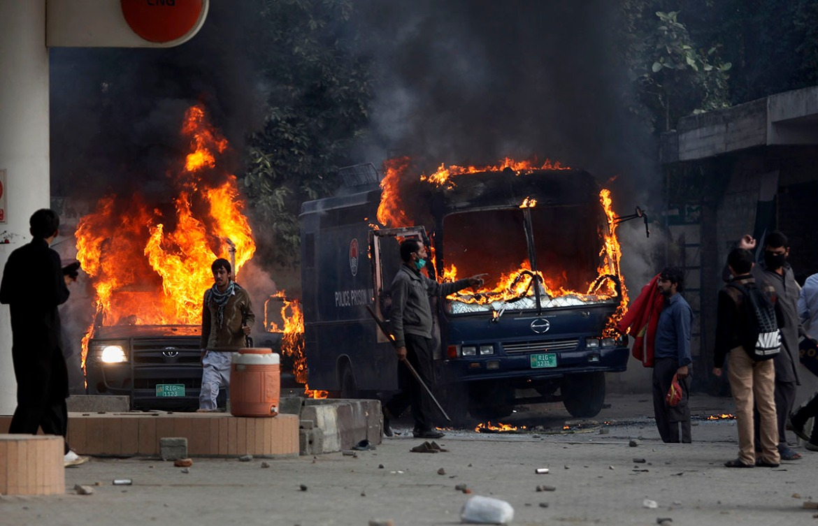 Pakistani protesters gather next to burning police vehicles after setting on fire them during a clash in Islamabad. [Anjum Naveed/AP Photo]