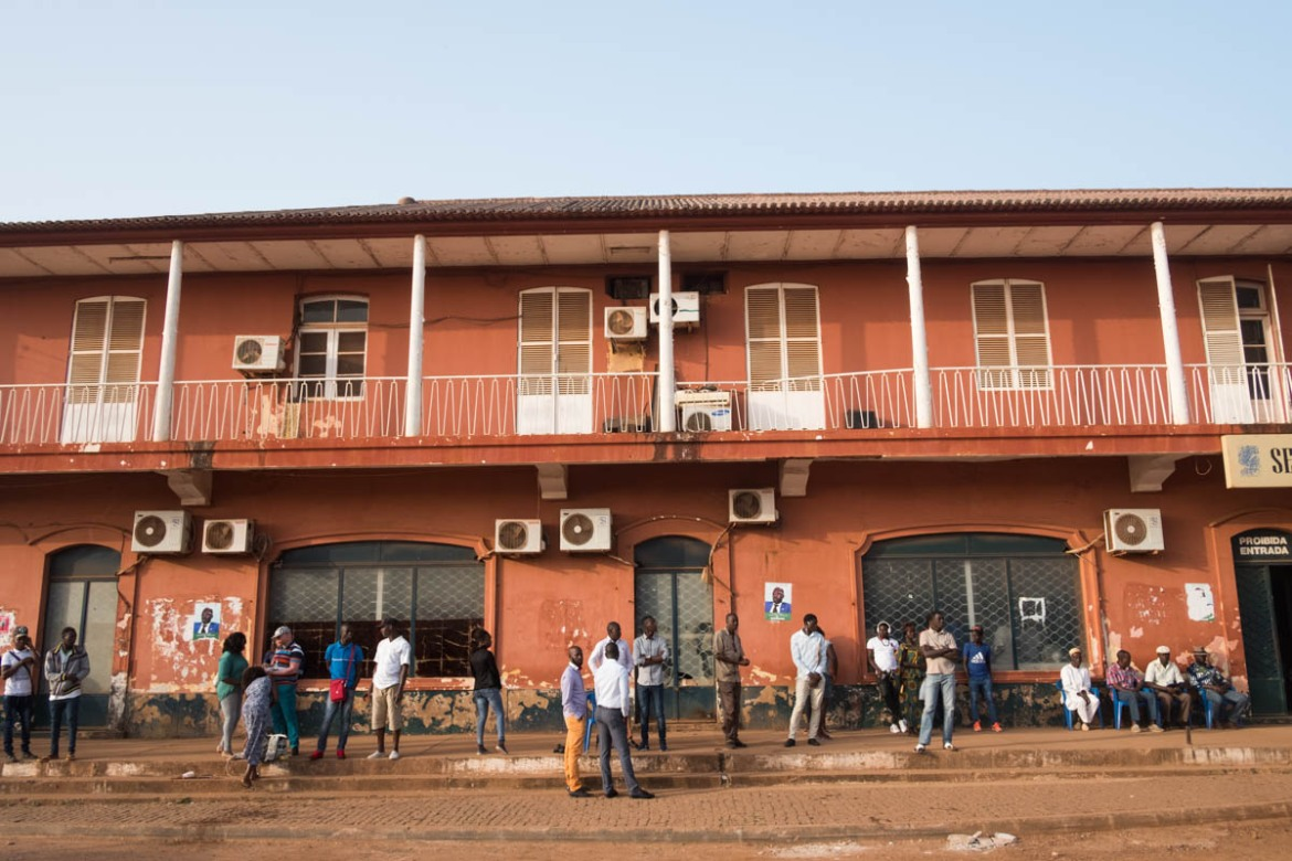 People gather outside a government building on Amilcar Cabral Avenue in Bissau. [Ricci Shryock/ Al Jazeera]
