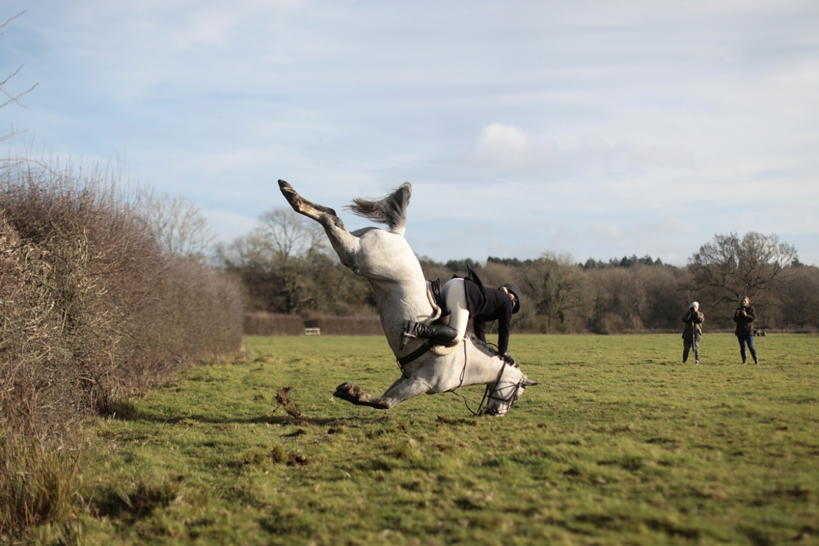 A member of the Old Surrey Burstow and West Kent Hunt crashes as she jumps a fence during the annual Boxing Day hunt in Chiddingstone, Britain. [Simon Dawson/Reuters]