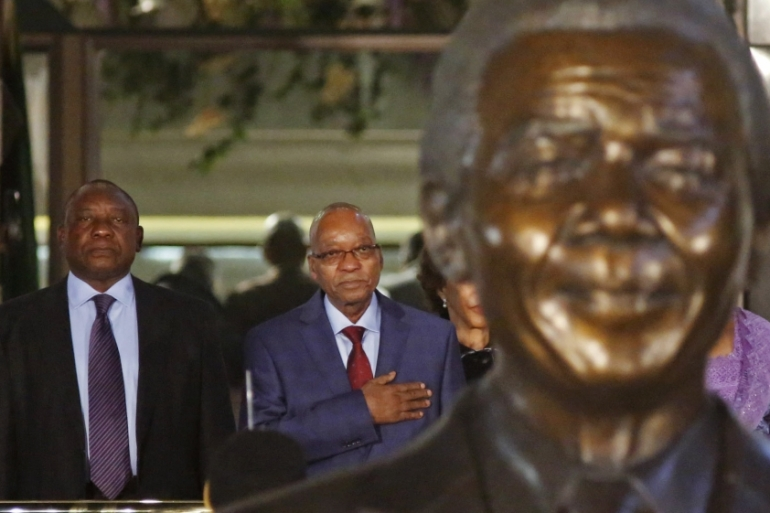 South Africa's President Jacob Zuma and Deputy President Cyril Ramaphosa stand behind a statue of former President Nelson Mandela outside Parliament in Cape Town [Schalk van Zuydam/Reuters]