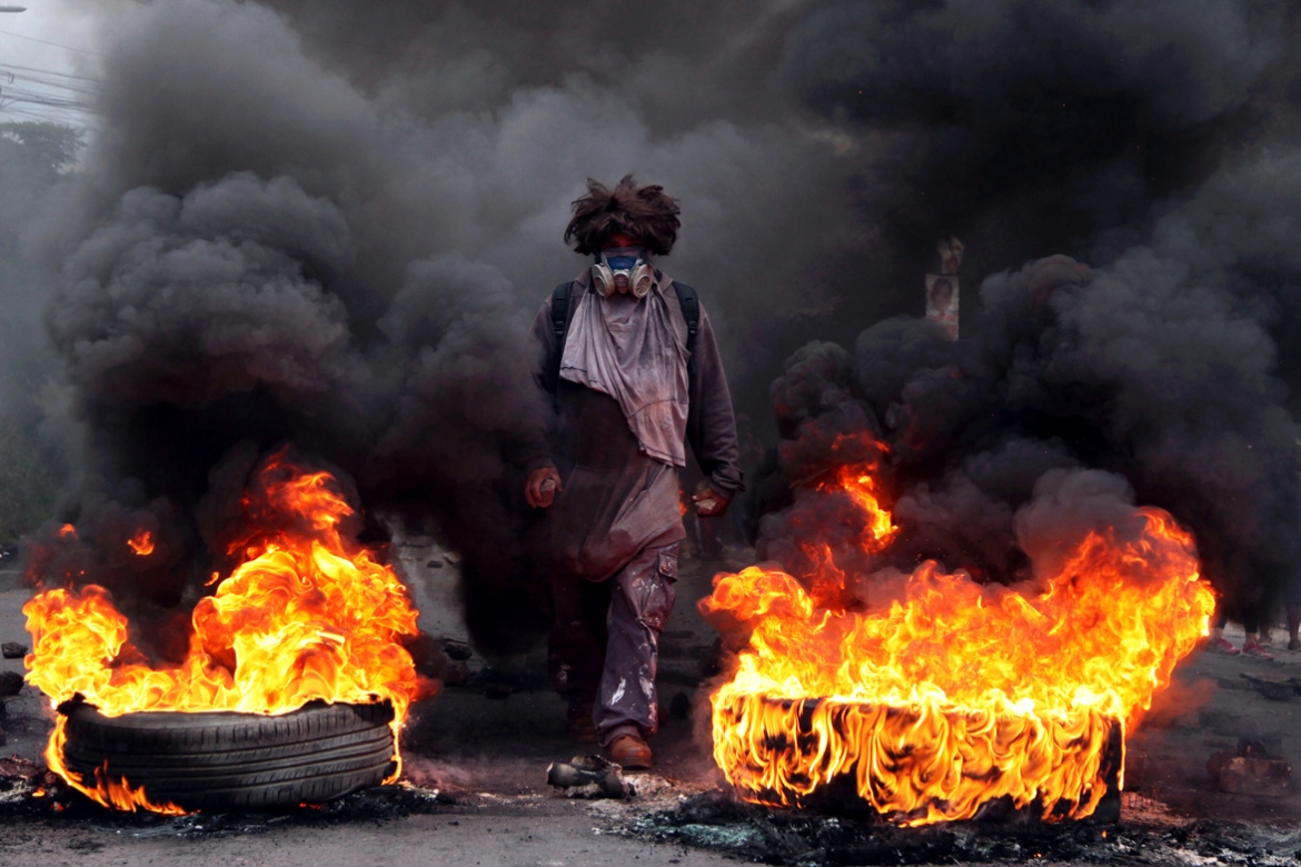 An anti-government protester blocks a road on the outskirts of Tegucigalpa, Honduras. The US administration recognised the results of Honduras' disputed presidential election despite opposition complaints, irregularities found by poll observers and calls from Congress to back a new vote. [Fernando Antonio/AP Photo]