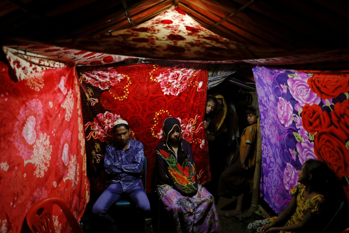 Rohingya refugees Saddam Hussein, 23, and Shofika Begum, 18, pose for a picture in a tent decorated with blankets just after getting married at the Kutupalong refugee camp near Cox's Bazar, Bangladesh. The newlywed couple, both from the village of Foyra Bazar in Maungdaw township, which was burned by the Myanmar military, fled with their families and other Rohingya some three months ago, Hussein said. [Damir Sagolj/Reuters]