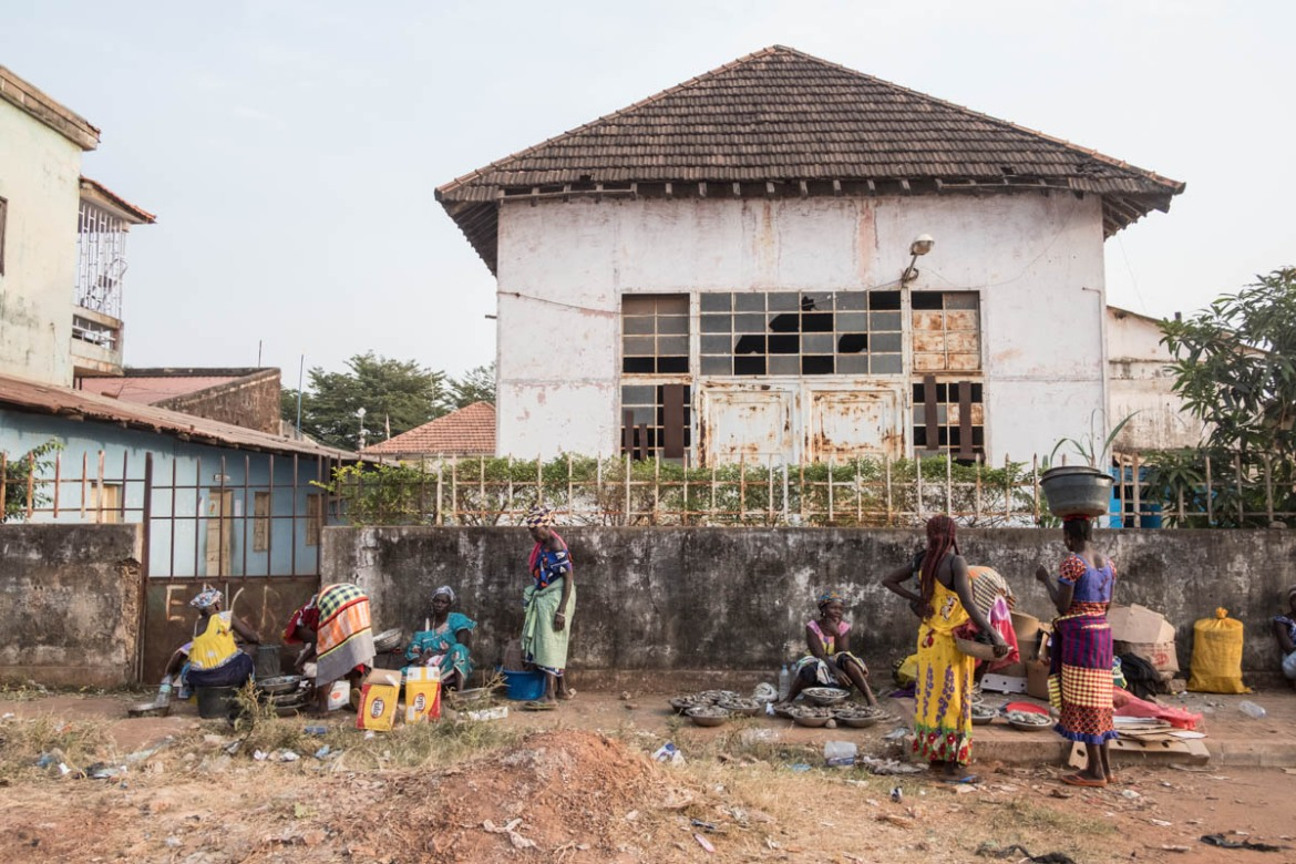 Women sell oysters in downtown Bissau next to an abandoned building. [Ricci Shryock/ Al Jazeera]
