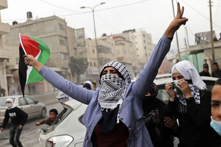 A protester in the West Bank waves her flag during clashes with Israeli security forces as protests continue over the US move on Jerusalem [Thomas Coex/AFP]