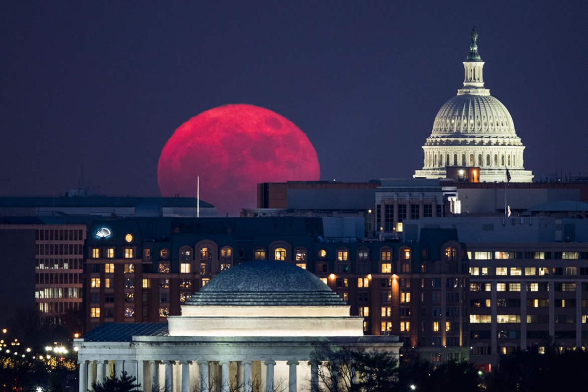 The moon glows red as it rises over Washington, DC. [Jim Lo Scalzo/EPA-EFE]