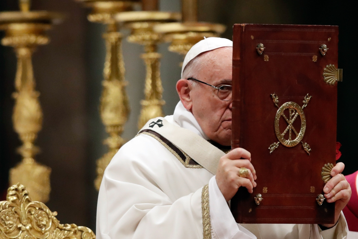 Pope Francis holds the Book of the Gospel as he celebrates the Christmas Eve Mass in St Peter's Basilica at the Vatican. [Alessandra Tarantino/AP Photo]
