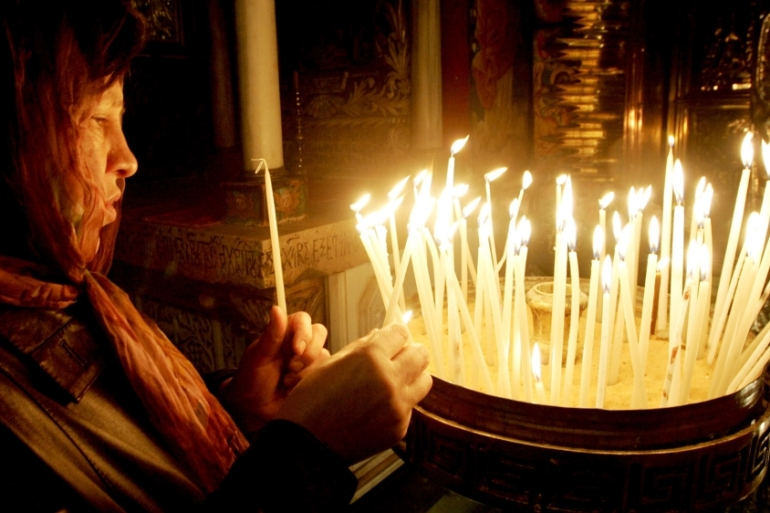 A Christian woman lights candles inside the Church of the Holy Sepulchre in Jerusalem's Old City before Christmas [Reuters/Eliana Aponte]
