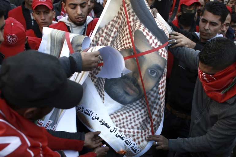 Palestinian Popular Front for the Liberation of Palestine supporters burn photos of Saudi King Salman and Saudi Deputy Crown Prince Mohammed bin Salman on December 9 [AP/Khalil Hamra]