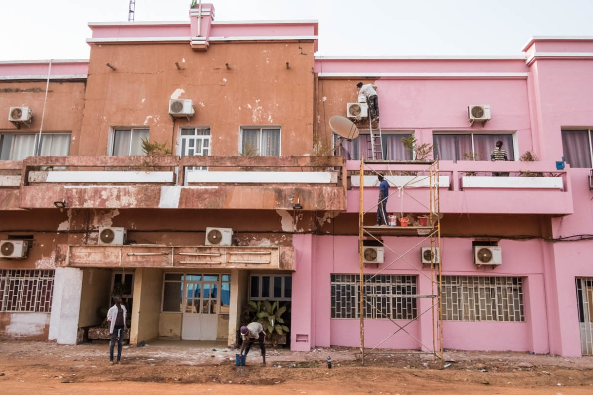 Workers renovate a building , which will be the Ministry of Commerce, in Old Bissau. [Ricci Shryock/ Al Jazeera]