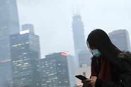 A woman wearing a mask walks to a subway station in Beijing amid the air pollution [File: Andy Wong/AP]