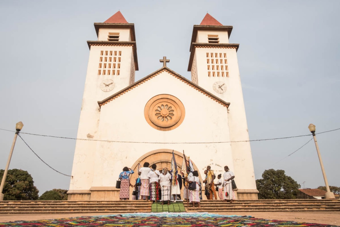 Women attend a wedding at Bissau's main Catholic church, the Cathedral of Our Lady of Candelaria. It was built by the Portuguese, and also serves as a lighthouse and sits along Amilcar Cabral Avenue. [Ricci Shryock/ Al Jazeera]